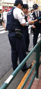 薬物関連を疑い任意で職質をする警察官(写真・編集部)。